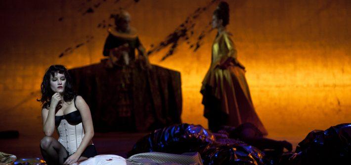 Zum ersten Trommelwirbel entrollt sich das Bühnenbild (Jens Kilian) in Gold von oben hinweg über die Bühnenschräge. Die Figuren, allesamt in ständigen Variationen darauf positioniert wirken wie kleine Marionetten, mögen ihre Gewänder noch so golden funkeln. Der skurrile Mix aus bizarren Barockreifröcken, steifen Renaissancehalskrausen und chicen Partydress parodiert die Macht ihrer Träger, entrückt sie durch die raffinierte Lichtregie (Olaf Freese und Irene Selka) als Grenzgänger zwischen Diesseits und Jenseits, die nichts als große Schatten werfen und tot auf der Drehbühne drapiert zur Allegorie eine Lebenskreislaufs zwischen Lust und Mord mutieren.