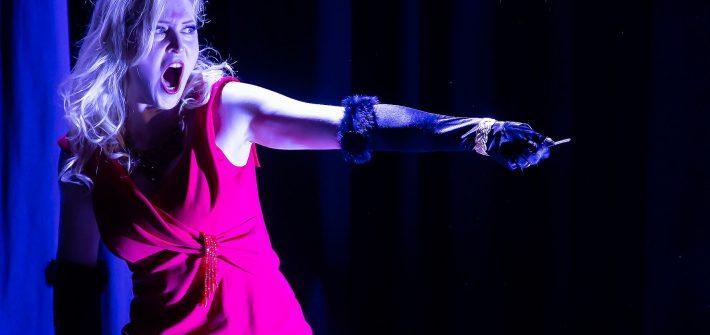 """Statt der Ouvertüre öffnet sich der rote Samtvorhang im Dorfener Jakobmayer-Jugendstilsaal und Tosca singt ein beschwingtes Chanson. Es wird in melancholischer Abdunklung zum Leitmotiv zwischen den Akten einer überaus spannenden """"Tosca""""-Inszenierung, mit der die Opera Incognita in Dorfen bei der Vorpremiere begeisterte.Mit einem Miniorchester von nur sieben Instrumenten und verringerten Nebenrollen auf der Bühne stemmt die Opera Incognita Puccinis rasante """"Tosca"""" in einer Bearbeitung von Ernst Bartmann, dem musikalischen Leiter,"""